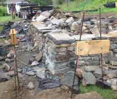 Rebar and wood frames used for right angle in dry stone wall foundation